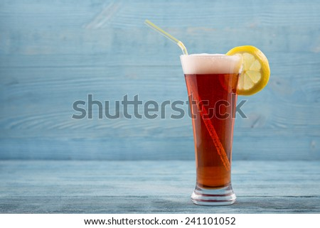 Glass of beer with lemon and sipper - stock photo