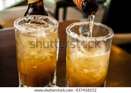 Glass of beer with mexican michelada mix and salt on the table. - stock photo