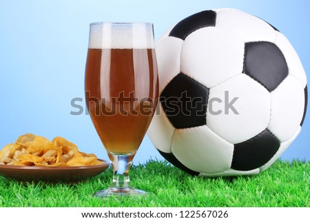Glass of beer with soccer ball on grass on blue background