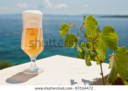 Glass of beer with the leaves of wine - stock photo