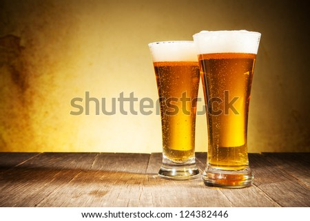 Glass of beers on wooden table - stock photo