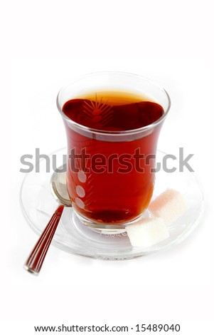 Glass of black-tea with cube sugar - stock photo