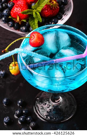 glass of blue alcohol cocktail in glass with cherry - stock photo