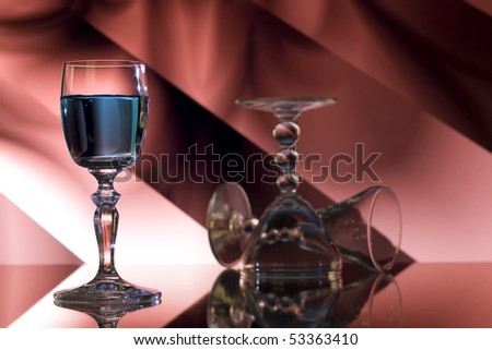 Glass of blue liqueur on red abstract background - stock photo