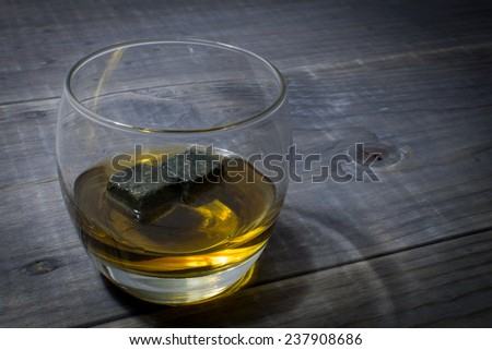 Glass of Bourbon with Whisky Stones on a Vintage Wood Farm Table - stock photo