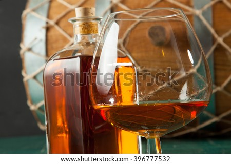 Glass of brandy and bottle on a green table top, against a background of old barrels