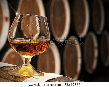 glass of brandy in the cellar with old barrels stacked in a row - stock photo