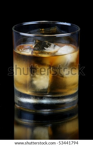 Glass of brandy or whiskey with ice blocks - stock photo