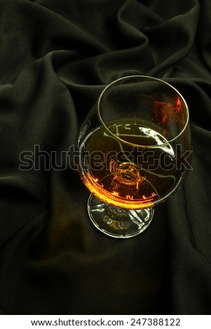 Glass of brandy standing on a crumpled black fabric