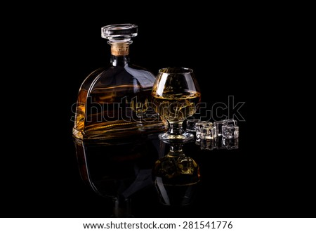 Glass of brandy with ice cubes and bottle on black background - stock photo