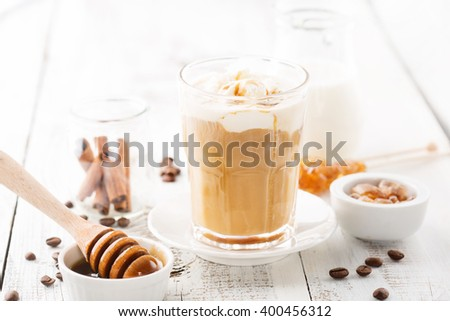 Glass of caramel latte coffee with whipped cream and coffee beans on a white wooden table, selective focus
