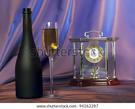 Glass of champagne and bottle.Red- blue background with hours