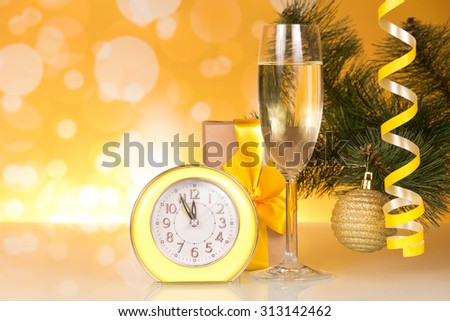 Glass of champagne and clock over fir tree branches