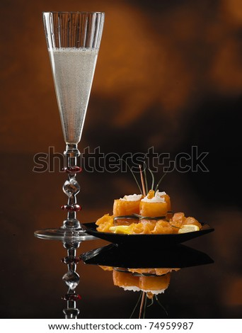 Glass of Champagne and Salmon Rolls With Reflection on Abstract Background - stock photo