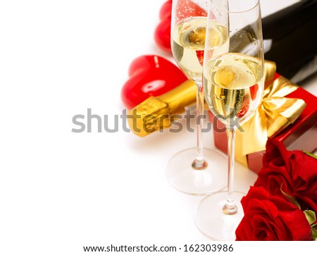 Glass of champagne, red roses and gift box over white background and copy space