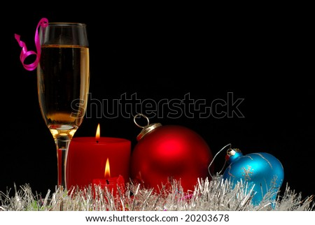 Glass of champagne with ribbons and candles against dark background