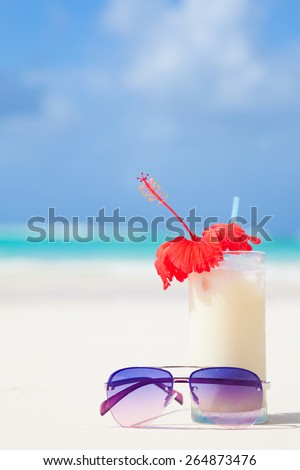 glass of chilled pina colada and sunglasses on the beach - stock photo