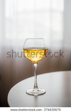 Glass of chilled white wine on wooden table - stock photo