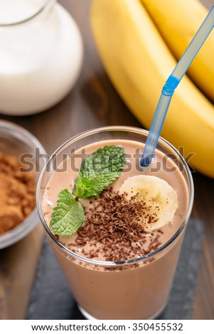 Glass of chocolate banana smoothie with straw top view - stock photo