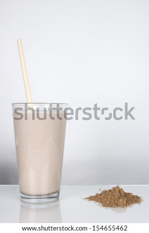 Glass of Chocolate Milk with Stirrer and Powder