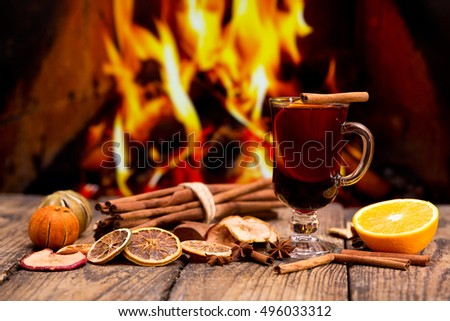 Glass of christmas mulled wine on wooden table against fireplace