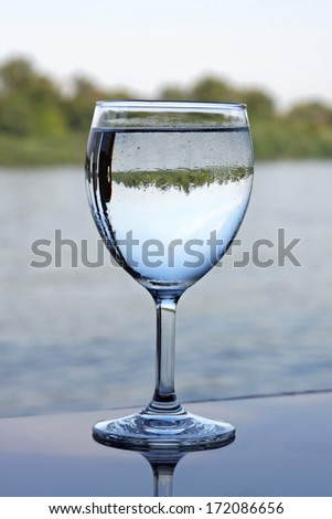 Glass of clean water at river
