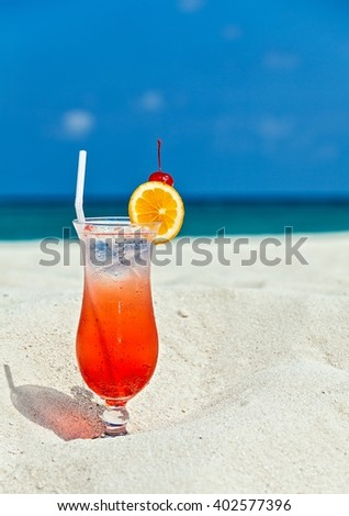 Glass of cocktail is on sandy coral  beach, Maldives, The Indian Ocean
