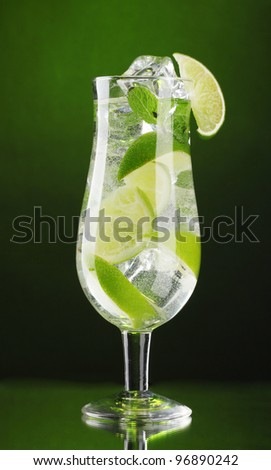 glass of cocktail with lime and mint on green background - stock photo