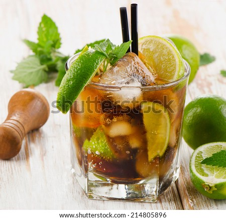 Glass of cocktail with rum, lime, mint  and ice on a wooden table. Selective focus - stock photo
