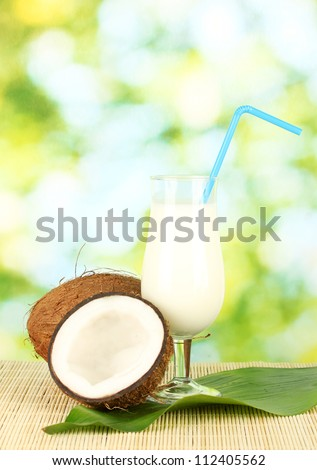 glass of coconut milk and coconuts on green background close-up