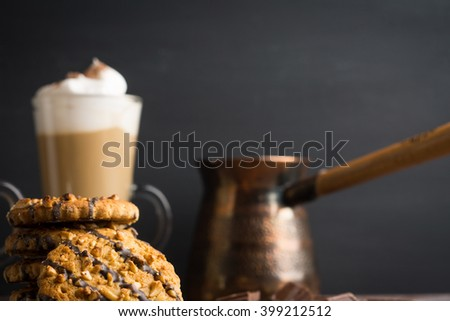 Glass of coffee with cookies on dark wooden background