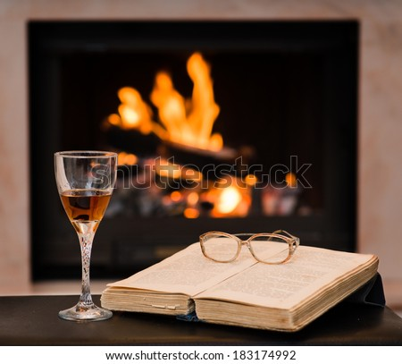 glass of cognac and book by the fireplace - stock photo