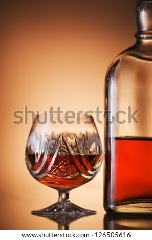 Glass of cognac and bottle close up - stock photo