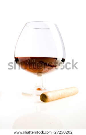 Glass of cognac and cigar on white ground