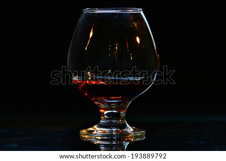 glass of cognac on black background - stock photo