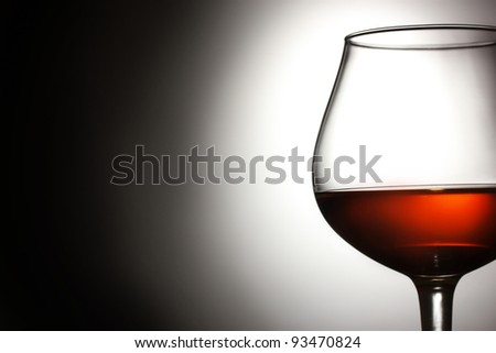 Glass of cognac on grey background - stock photo