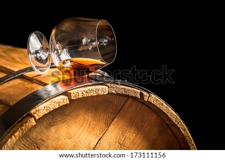 Glass of cognac on the vintage barrel - stock photo