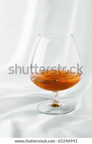 Glass of cognac on white silk - stock photo