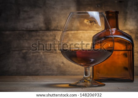 Glass of cognac with bottle - stock photo