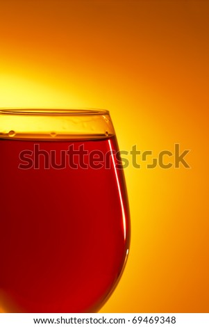 Glass of cognac with candle reflection - stock photo
