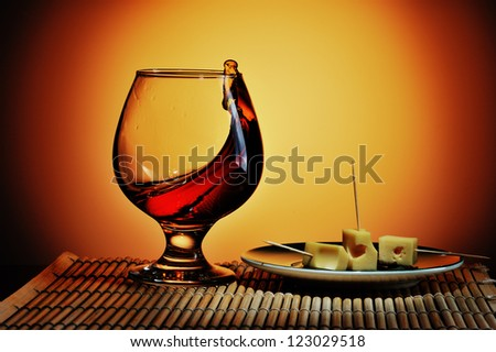 Glass of cognac with cheese plate