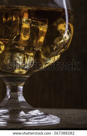 glass of cognac with ice closeup  on cloth background - stock photo