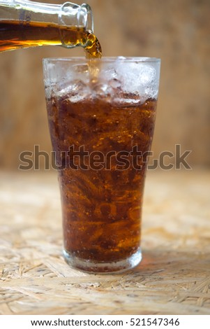 Glass of cola being poured into ice glass