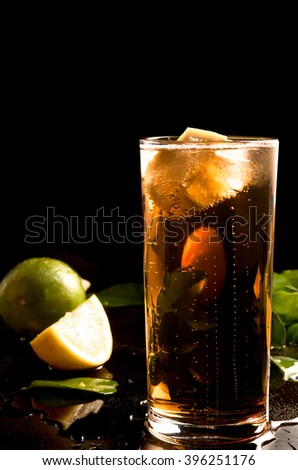 glass of cola or coke with ice cubes, lemon slice and mint  - stock photo