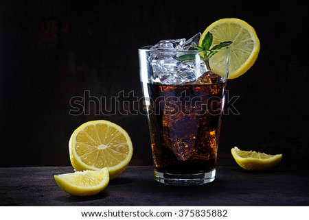 glass of cola or ice tea with ice cubes, lemon slices and peppermint garnish on a wooden table against a dark brown wall, copy space, selected focus - stock photo