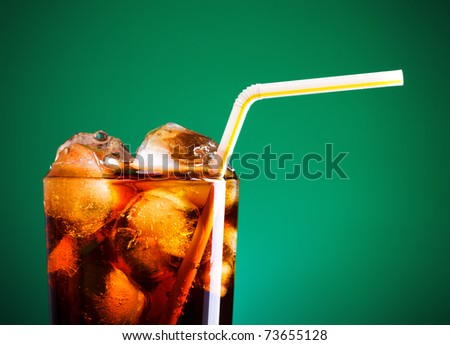 glass of cola with ice and straw on green background - stock photo