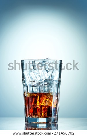 Glass of cola with ice cubes on a blue background - stock photo