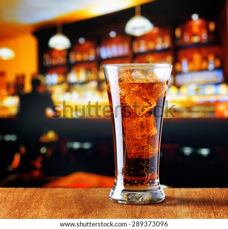 Glass of cola with ice in a bar. - stock photo
