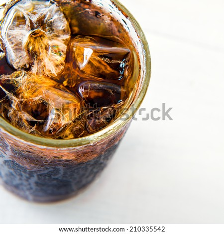 Glass of cola with ice on wood board - stock photo
