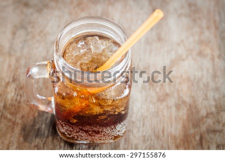 Glass of cola with ice on wooden table, stock photo